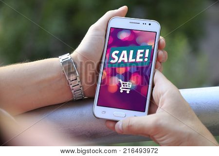 Girl at balcony with smartphone a sale advertising on the screen. Cell phone publicity. Ecommerce, internet marketing.