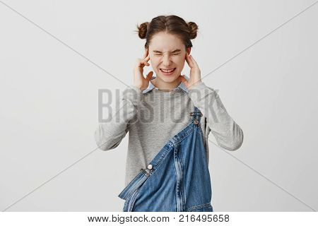 Young woman plugging ears with fingers and screwing up her eyes in displeasure. Brunette female 20s covering ears not listening ignoring conversation. Human reactions and attitude