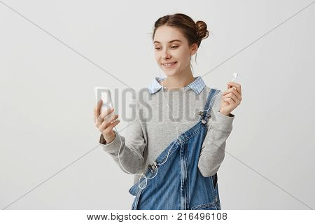 Beautiful lady in denim overalls looking on her iPhone smiling widely. Modern friendly wife talking on Skype with her husband while being away on business. Communication concept