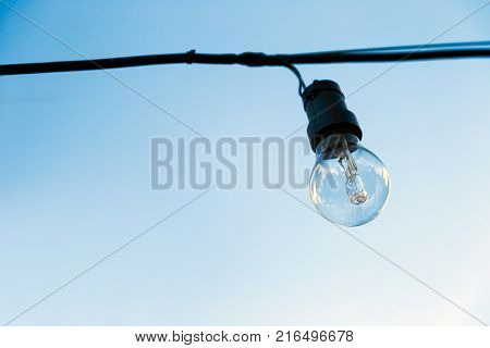One light bulb off, hanging on a cable in exterior. The blue sky at background.