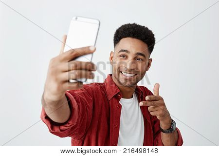 Say cheese. Close up of young beautiful dark-skinned man with afro hairstyle in casual white t-shirt and red shirt smiling with teeth, holding smartphone, making selfie photo