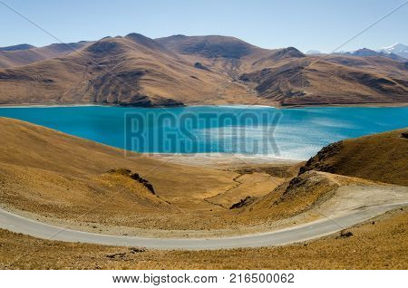 Panoramic view of Tibet natural landscape blue azure water lake surrounded desert mountains.