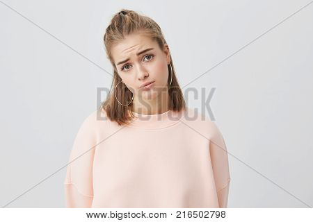 Beautiful young european female with fair hair looking at camera with unhappy and regretful look against gray background. Sad pretty girl feeling upset while spending time at home alone.