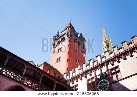 Low-angle view of Basel town hall tower and golden steeple against blue sky, Switzerland
