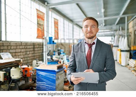 Portrait of successful sales assistant wearing suit posing looking at camera and smiling , standing in showroom selling industrial machine tools
