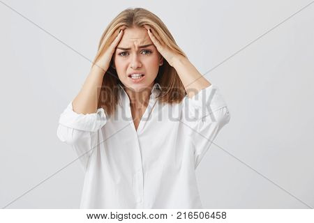 Frustrated young woman having terrible headache keeping hands on head frowning her face with pain looking unhappy and stressful. Female student in despair having stressful situation at university.