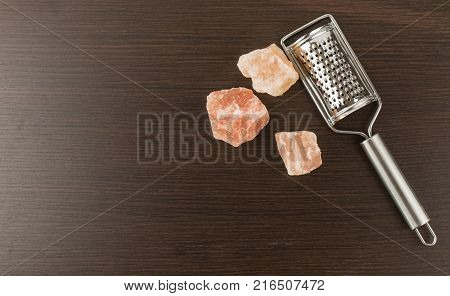 Himalayan salt with grater. Pink Himalayan salt with grinder on wooden background. Metal silver grater and red salt.