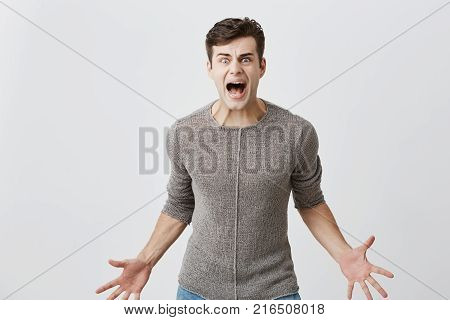Annoyed caucasian man holds hands in furious gesture, screams loudly as has quarrel with wife, sorts out family relationship indoors. Furious angry male shouting, expressing negative emotions.