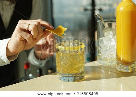 Mixologist is decorating a drink with piece of beeswax