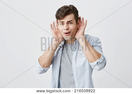 People, emotions, reaction, face expressions concept. Handsome shocked puzzled european male keeps opened palms behind his ears, keeps mouth widely opened, being in stupor, not believing in words he heard.
