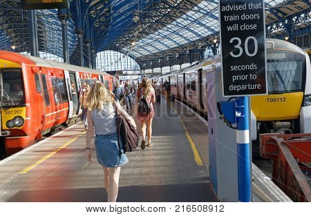 BRIGHTON GREAT BRITAIN - JUN 19 2017: People walking on the platform to catch a train in the train station in Brighton UK. June 27 2017 in Brighton Great Britain