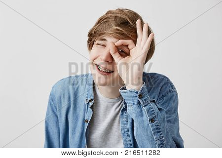 Positive young man with fair hair closing his eyes and smiling with joy showing ok sign being glad after meeting with his girlfriend isolated against gray background. Human face expressions and emotions