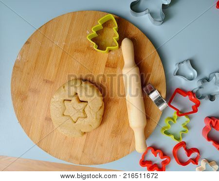 Making homemade Christmas cookies. Rolling pin cookie cutters and cookie dough on wooden board overhead view