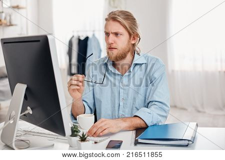 Serious concentrated pensive male businessman wears blue shirt holds spectacles in hand, works on computer, thinks about financial report, sits against light office interior. Thoughtful bearded manager or freelancer drinks coffee and generates new ideas