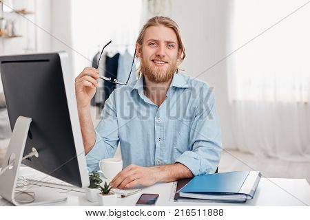 Handsome cheerful bearded young fair-haired male copywriter types information for advertisment on website, wears blue shirt and spectacles, sits at coworking office in front of screen, uses modern computer for work