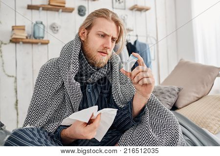 Sick bearded fair-haired young man in sleepwear sitting on bed surrounded by blanket and pillows, frowns while reading prescription on pills, holds white handkerchief in hand. Health problems, bad cold and flu.