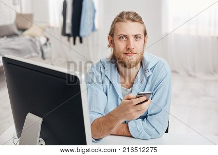 Bearded good-looking male office worker with gentle smile reads notification on smart phone, sits in front of screen at coworking space with cell phone, sends messages, gets job offer on email box, sends feedback to coworkers, browses internet