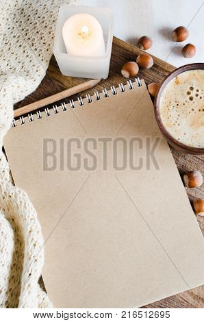 Business holiday or new year planning concept : Desk table with plaid notebook paper candle and coffee cup Top view or flat lay with copy space ready for adding or mock up