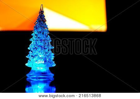A small blue lighting Christmas tree on the contrast dark and orange geometric background. Selective focus reflections geometric lines. Abstract colorful Christmas background.