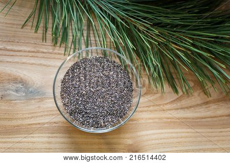 chia seeds in a glass bowl on a wooden table near the spruce branch. Organic chia seeds.Healthy food,superfood or bodycare concept