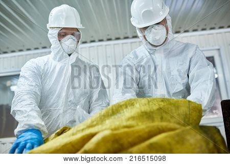 Low angle portrait of two workers  wearing biohazard suits working at waste processing plant sorting recyclable materials on conveyor belt