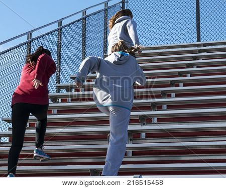 High school girls warm up on a fall day by running bleachers before practice on a sunny fall afternoon.