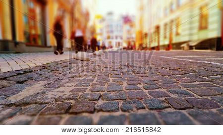 Old town street with stone pavement blurred cars and pedestrians in vintage colors with selective focus effect