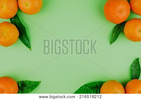 Green backgroung with mandarins and mandarin leaves . Top view. Citrus background. Citrus mandarins frame with copyspace