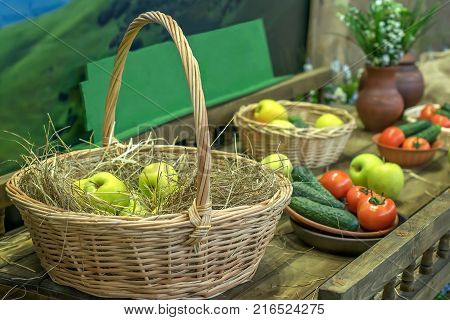 still life of fruit and vegetables and apples in a basket with straw pastoral motifs