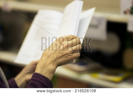 Close-up of hands of the elderly person with open book, bookstore, library. Real scene. Education concept, Self-study, reading fiction, pension, interests in the elderly, life style