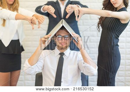 American man sitting While using Laptop Computer Cover his head During Group of Partner Bad Complaint over head.Closeup.Unlike Concept.