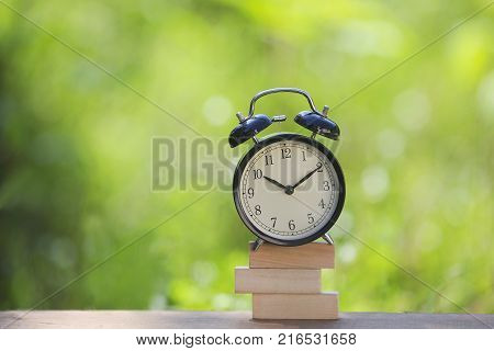 Black alarm clock stacked on wooden bar with shallow DOF green background. Business / Time Management concept