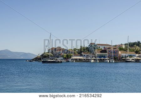 vote sail sailing in the fiskardo bay behind houses that surround the port of the same name as the bay and finally the mountains of the greek island of kefalonia