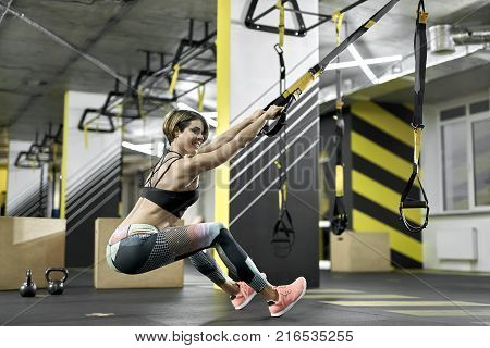 Smiling girl is training with TRX straps in the gym. She relies on her feet on the floor while her hands are holding the straps. Woman wears colorful pants with black top and pink sneakers.