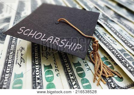 A Scholarship graduation cap on assorted money