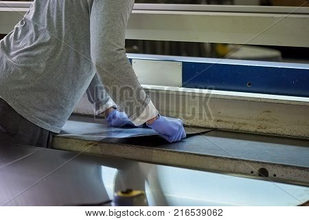 Man is thrusting a metal sheet in a slit. Worker is thrusting a thin metal sheet in a slit.