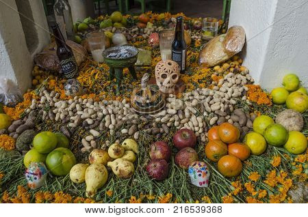 OAXACA, OAXACA, MEXICO- NOVEMBER 1, 2017: Traditional mexican Day of the Dead offering altar with fruit,flowers,sugar skulls and ornaments in Oaxaca, Mexico