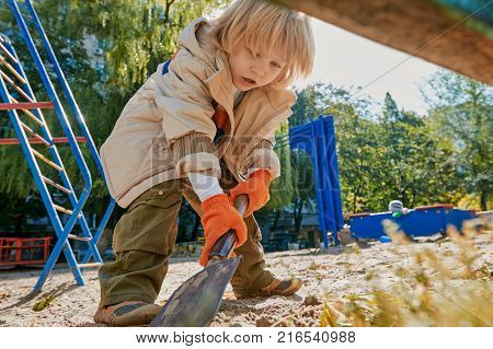 Cute boy having fun with sand and shovel on outdoor playground