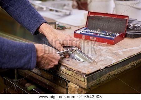Fastener screwing. Worker is screwing a fastener using hand screwdriver.