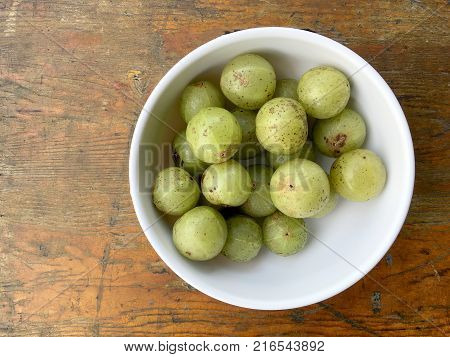 Delicious Indian Gooseberry In A Small White Blow On Wooden Table, Local Fruits And Herbs With Medic