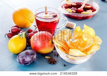 Winter alcoholic drinks - mulled wine, punch, grog with cornflakes Glass glasses with mulled wine. Hot fruit tea. Spices, fruit.