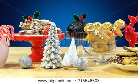 Festive table with traditional English and European style Christmas food including panforte cake, plum pudding, gingerbread cookies, and chocolate covered shortbread.