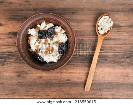 Clay bowl with cottage cheese, raisins and dried apricots near to the wooden spoon, top view. Dairy product cottage cheese in ceramic bowl on old wood table. Template for menu or print design.