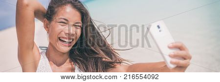 Summer fun vacation woman taking selfie banner laughing. Happy Asian woman taking self-portrait pictures with mobile phone on tropical beach holidays in Caribbean taking photos.