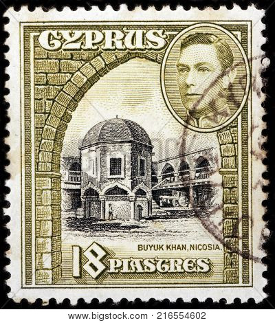 LUGA RUSSIA - OCTOBER 17 2017: A stamp printed by CYPRUS shows portrait of King George VI and view of Buyuk Khan in Nicosia - the largest caravansarai on the island of Cyprus circa 1938