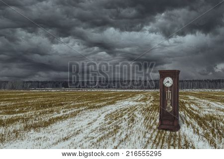 A vintage wooden clock in an autumn field. An unusual photo of the clock. It's a nasty day