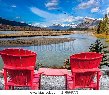 Two red comfortable loungers by the Abraham lake. Warm September in the mountains of Canada. Concept of ecological and active tourism