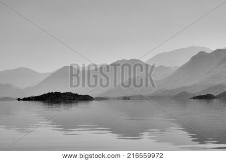 Silhouettes of misty hills over the water surface, lake Skadar in Montenegro
