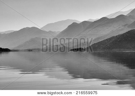 Reflections of misty mountains over the water surface, lake Skadar in Montenegro