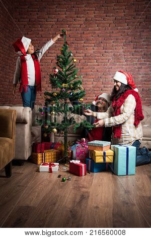 family, holidays, generation, christmas and people concept - smiling Indian grandparents and granddaughter with gift boxes decorating christmas tree at home